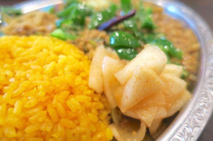 副菜は大根の漬物。おすすめ野菜1種のトッピングはピーマンで、たっぷり野菜を食べられる。