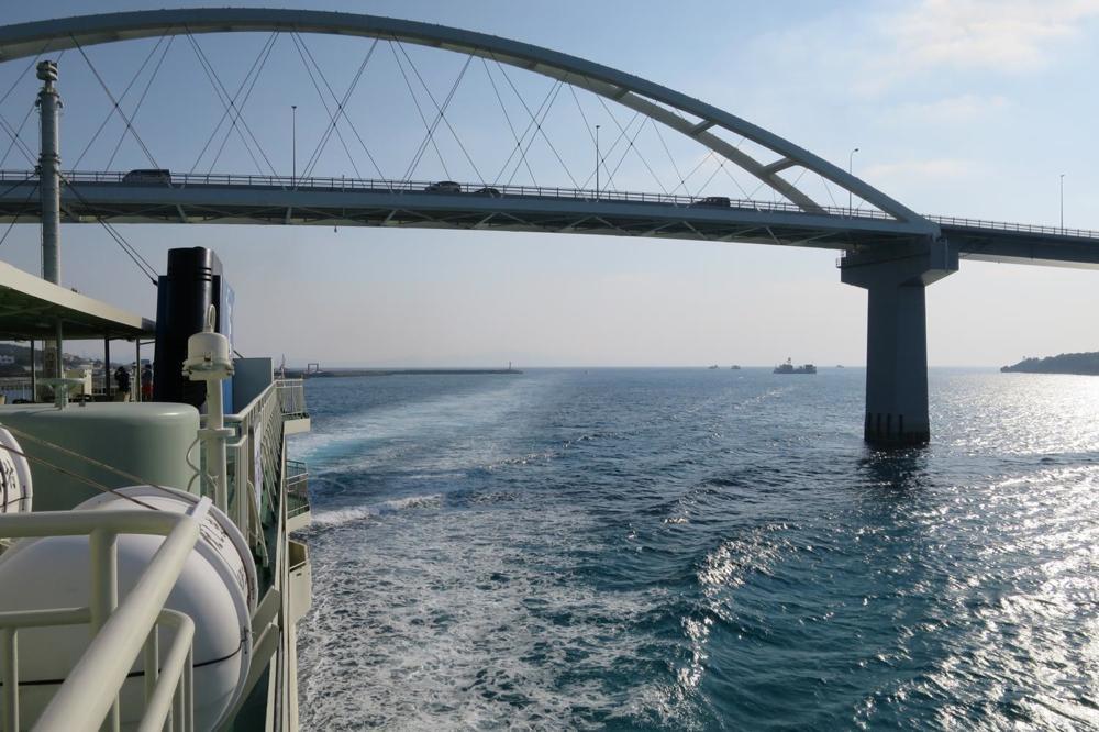 本部港から伊江島へ向かうフェリー「いえしま」がくぐり抜けた後の瀬底大橋。