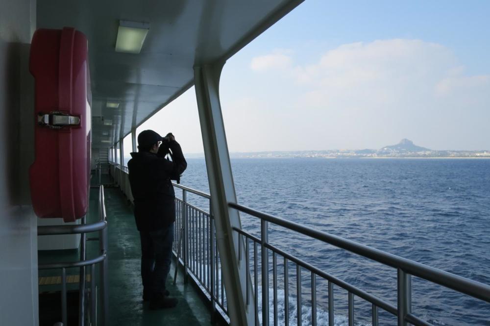 本部港と伊江島を結ぶフェリー「いえしま」で伊江島タッチューを撮影するオカモーさん