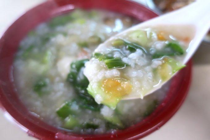 那覇・浮島通り「台湾風粥専門店 阿里(アーリー)」鶏粥(小230円)に野菜(50円)と塩卵(半分80円)をトッピング。熱々でボリューム満点。
