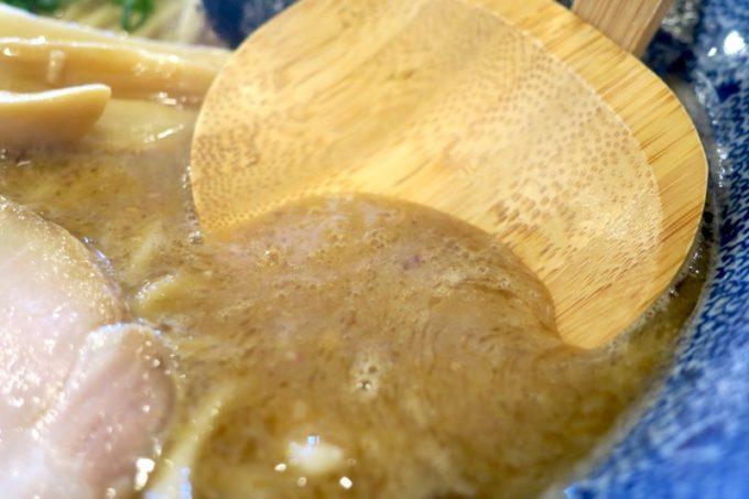 浦添「麺や偶 もとなり 牧港店」の特濃魚介中華SOBAのスープと木のレンゲ。