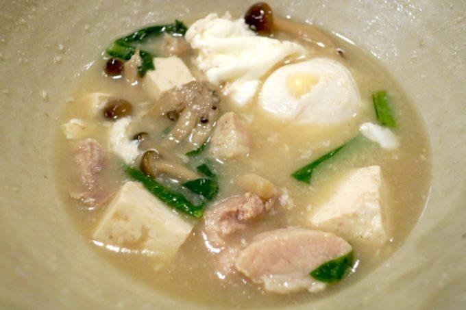 那覇・泉崎「味噌めしや まるたま」の具だくさん味噌汁に入ってる玉子、豚肉、島豆腐、青菜、きのこなど。