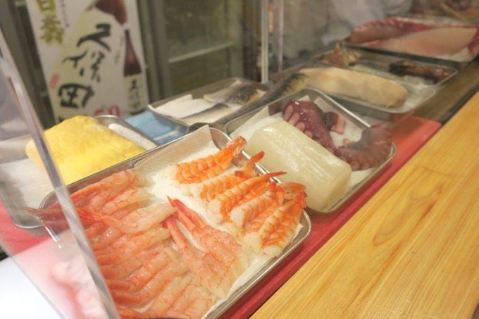 「栄町すし酒場 こめつぶ」のショーケースに並ぶ寿司ネタ