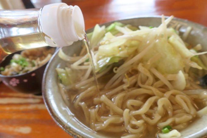 浦添市勢理客「東江そば」の野菜そばのスープに、コーレーグスをいれていただく。