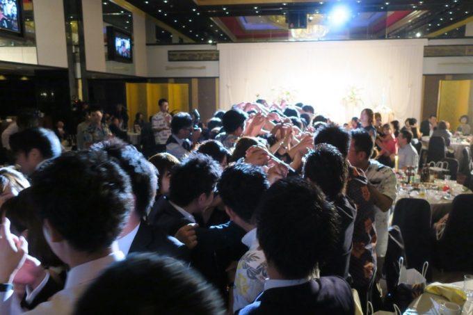 沖縄の結婚式の新郎新婦退場時に、急に立ち上がる参加者たち。