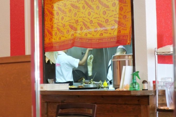 店内のガラスに写り込んだ、ナンを焼き上げる厨房スタッフ