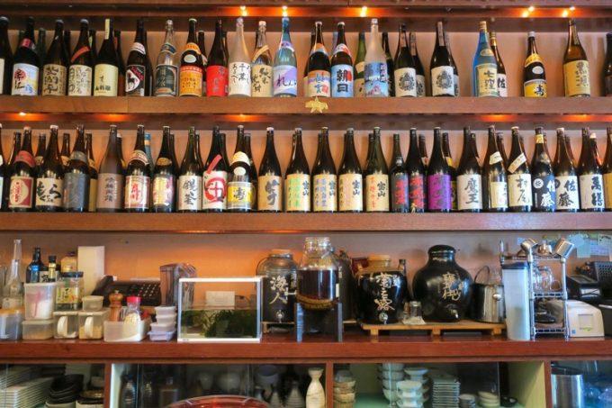 「沖縄料理と地頭鶏 炎」に並ぶ焼酎の一升瓶。圧巻です。