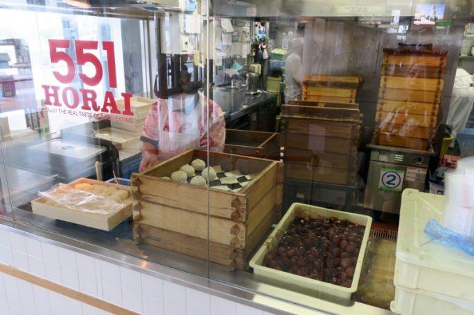 店内キッチンで肉まんを包み続けるお店の方がいる。