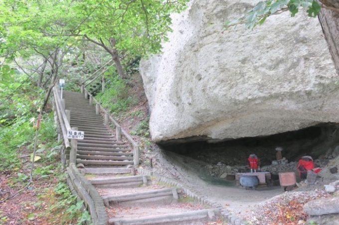 階段の先には駐車場がある。途中、巨大な岩の下にお地蔵さんが祀られていた。
