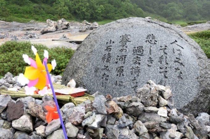 本山栄一という歌人の「人はみな それぞれ悲しき過去持ちて 賽の河原に 小石積みたり」という歌が刻まれた石。