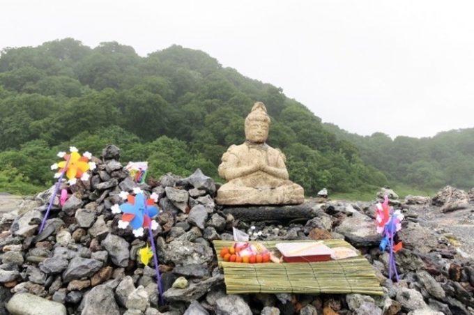 首に亀裂がある仏像と、お供え物。