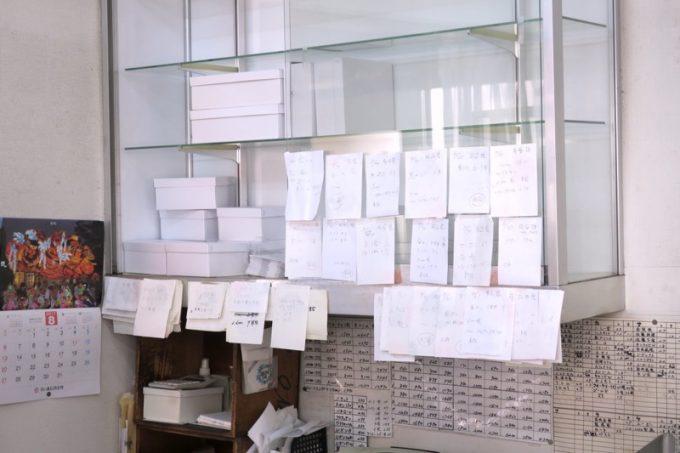 ガラス戸棚には、閉店を惜しむ注文客のメモがびっしり。
