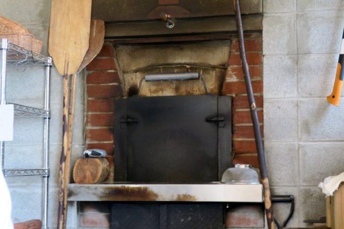 手作りの石窯には薪をくべてパンを焼き上げる。