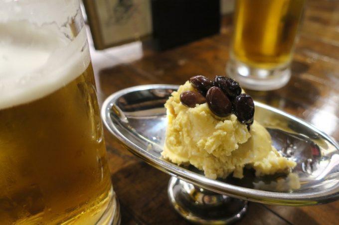北谷・美浜にある「新子屋(アラコヤ)」のビール(サントリーモルツ、450円)と、ポテトサラダ(380円)。