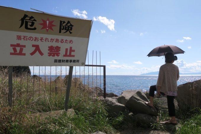 立ち入り禁止の看板と、岩場に足をかけるおかん。