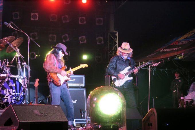 """「キャンプキンザーフェスティバル」のライブでギタープレイを魅せるYUKIO """"GG"""" SHIMOJIと清正。"""
