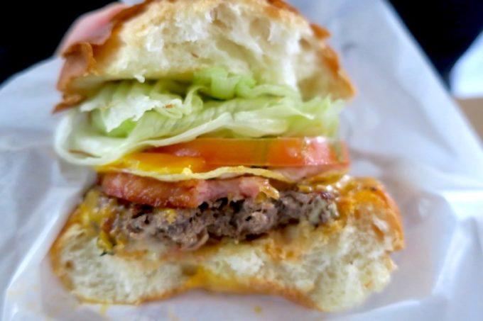 那覇・楚辺「Maverick(マーベリック)」のベーコンエッグチーズにかぶりついた写真。