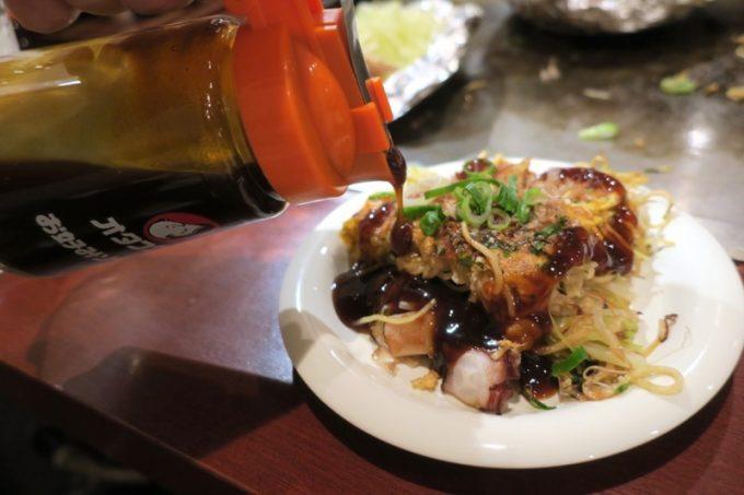 広島のお好み焼きには、どろりとしたソースをたっぷりかけていただきます。