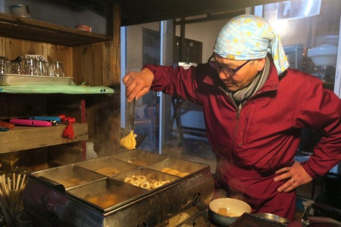 函館・大門「屋台ライダーキック」の店主におでんを取り分けてもらう。