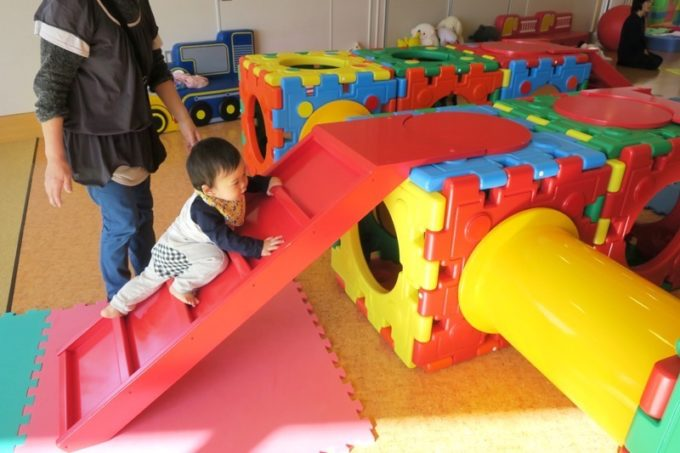 函館・道南四季の杜公園「ちびっこ広場」のキッズジムを登る1歳児。