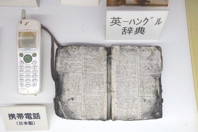 回収した携帯電話と英ハングル辞典。