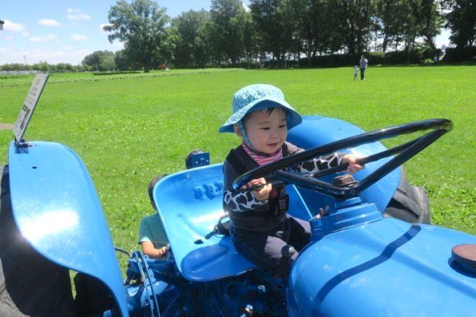 札幌「八紘学園 農産物直売所」で青いトラクターにまたがるお子サマー。