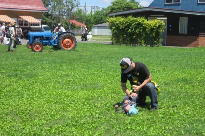 札幌「八紘学園 農産物直売所」の青いトラクターが気に入ってしまい、駄々をこねるお子サマー。
