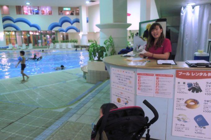「リザンシーパークホテル谷茶ベイ」のインドアプールカウンターで、館内アクティビティの受付を行う。