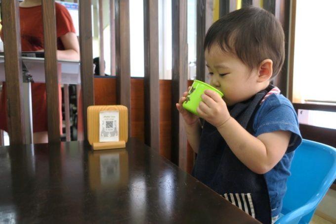 本部町「本部そば」の小上がり咳で、子ども用イスに座ってお水を飲むお子サマー。