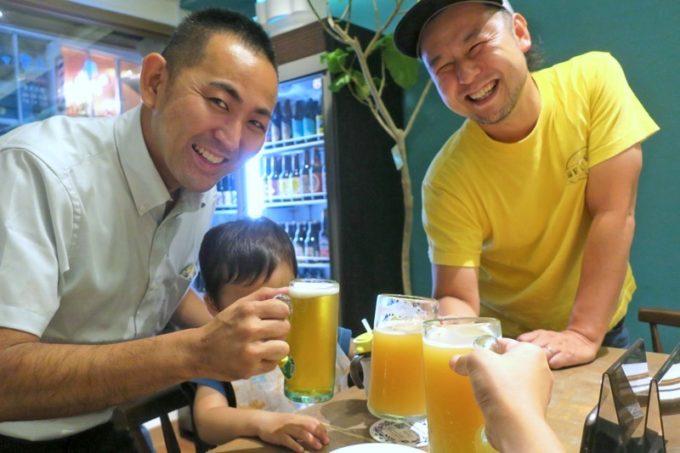 那覇・サンライズなは商店街「Taste of Okinawa(テイスト オブ オキナワ)」2周年を祝って、オーナーの護得久さんと乾杯。
