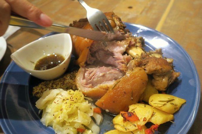 沖縄県産豚の前足をまるごと使用した、「Taste of Okinawa(テイスト オブ オキナワ)」のアイスバイン(1580円)を大胆にカット!
