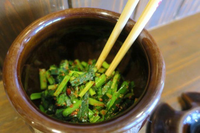 浦添・宮城「麺や 和楽」常連さんに習って壺ニラを投下。
