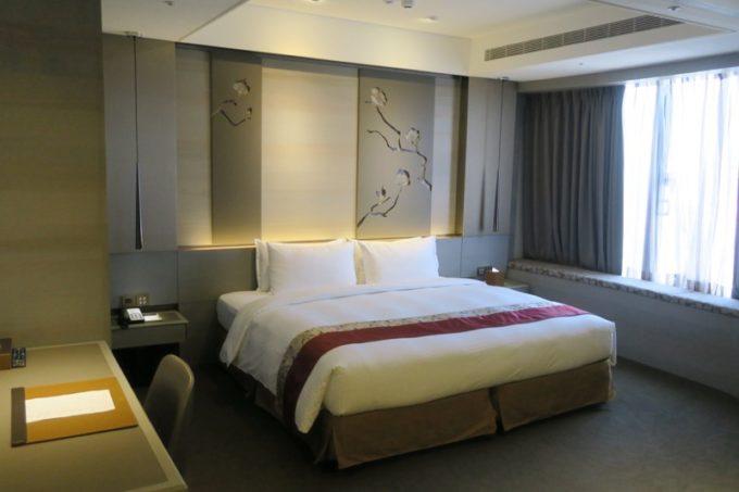 台北「グリーンワールドグランド南京(洛碁大飯店南京館)」のエグゼクティブスイートのベッドルームにはキングサイズのベッドが用意されている。
