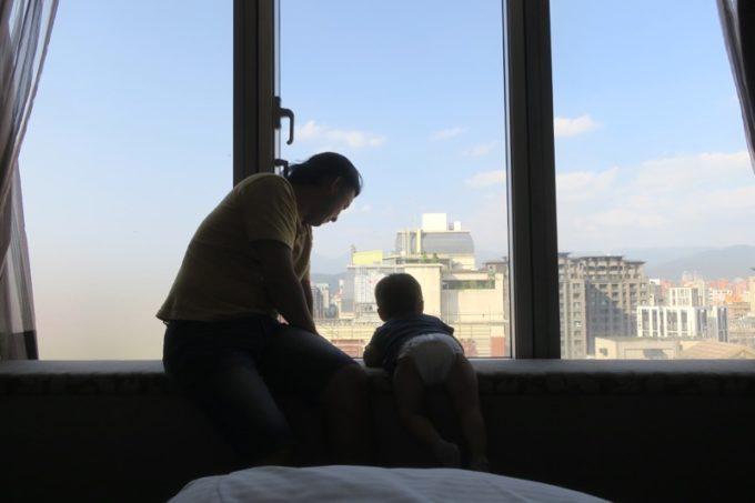 台北「グリーンワールドグランド南京(洛碁大飯店南京館)」のエグゼクティブスイートの窓辺で遊ぶ親子。