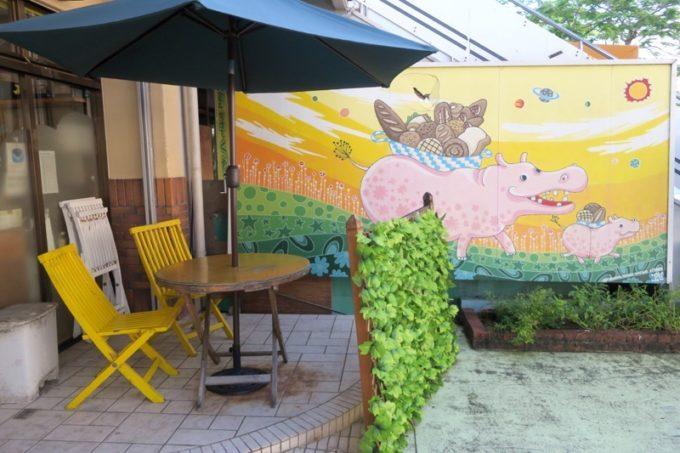 那覇・国場「カバのパン屋さん」の店先にあるテラス席と、壁に描かれたカバくん。