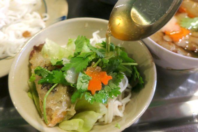 那覇・松尾のベトナム料理「ノイカフェ」お皿に麺とおかずとパクチーを盛り付け、つけ汁をかける。