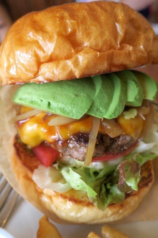 沖縄市・園田「RALPH'S BURGER RESTAURANT(ラルフズバーガーレストラン)」のアボカドチーズバーガーは具材がたっぷりで高さがある。