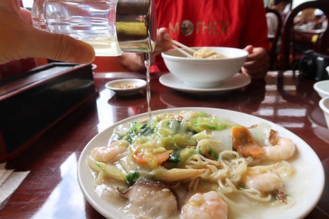中城村「担々亭 南上原店」蝦仁炒麺(エビかけ焼きそば、1050円)にお酢をたっぷりかけて味変する