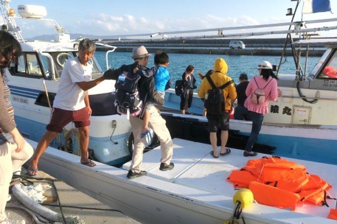 伊江島で漁船に乗り込むブロガーたち。