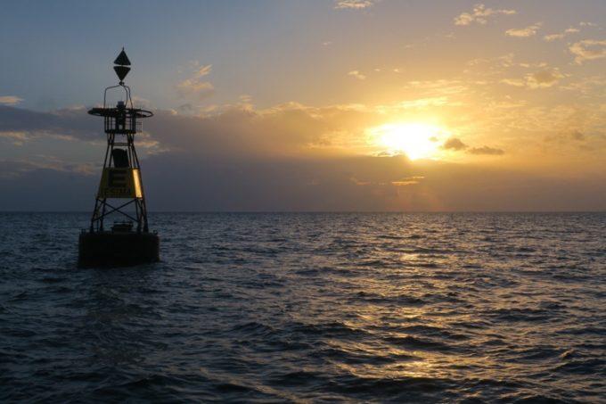 伊江島沖に浮かぶ金属製ブイと夕日。