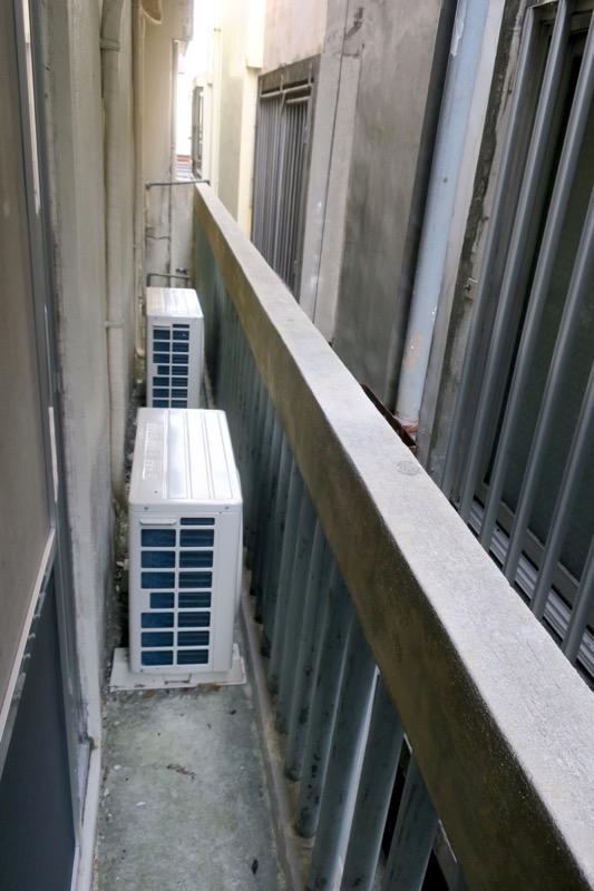 沖縄市「アーケードリゾートオキナワ ホテル&カフェ」の窓を開けると、エアコン室外機しか置けないベランダがあった。