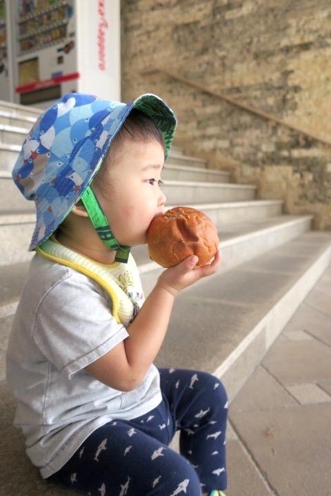 伊江港フェリーターミナル裏手「伊江島小麦直売所」で買ってきた麦パン(120円)を頬張るお子サマー。