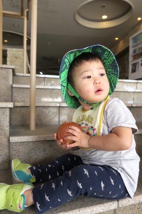 伊江港フェリーターミナル裏手「伊江島小麦直売所」で買ってきた麦パン(120円)を持ってモデル風なお子サマー。