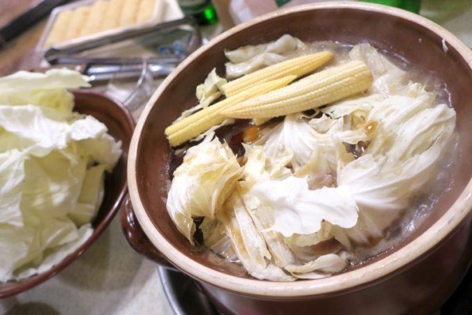 台湾・高雄「現殺霸味薑母鴨」食材に火が通ってきたら、キャベツやヤングコーンを追加。