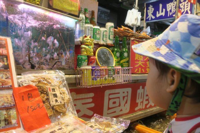 台湾・高雄の「六合夜市」の屋台先で動くエビに見入るお子サマー。
