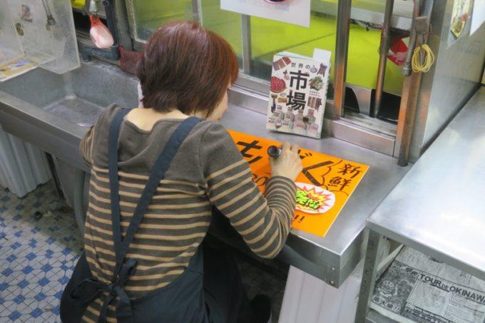 2019年6月16日で一時閉鎖する、那覇・牧志公設市場1階の様子(手書きのPOPを書く女性)