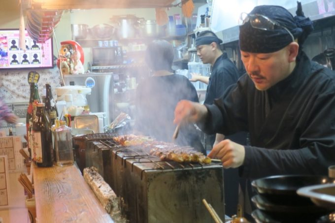 宜野湾・宇地泊「東京やきとり酒場」焼き場で煙をもうもうと立てながら焼鳥を焼く。