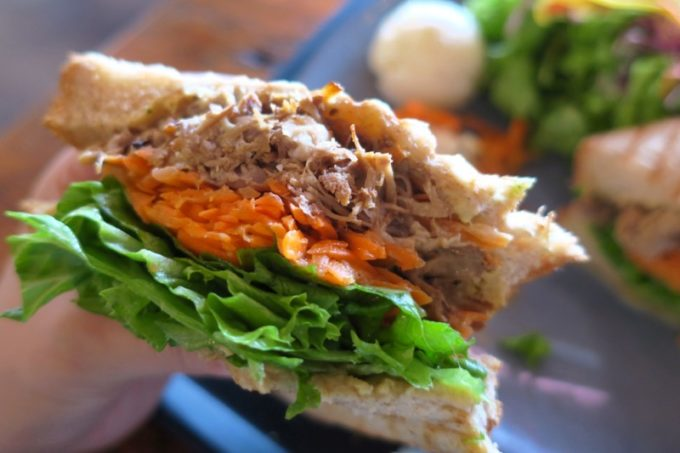 """北谷「VONGO & ANCHOR(ボンゴ・アンド・アンカー)」のサンドイッチ、プルドポーク""""ブリッツ""""を持ち上げてわかるサイズ感。"""