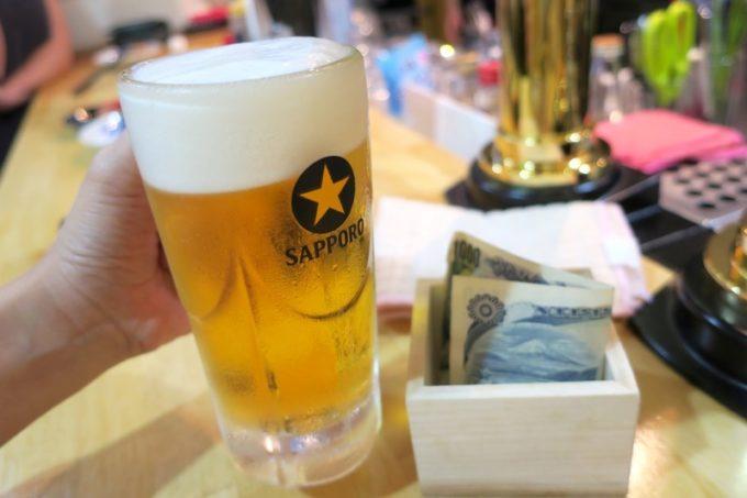 那覇・牧志「酔処 玉川(よいしょ たまりば)」サッポロビールの黒ラベル(450円)とキャッシュオンのお金を入れる升。