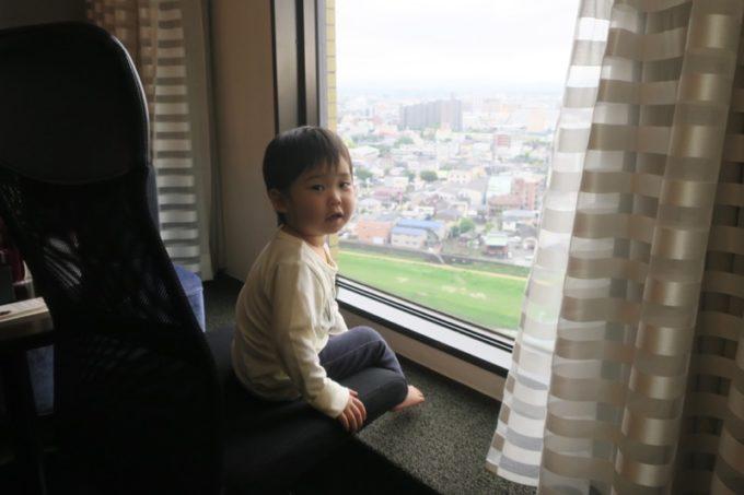 熊本「ANAクラウンプラザホテル熊本ニュースカイ」スーペリアツインの窓から熊本の眺めを楽しむお子サマー。